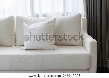 white decorative pillows on a casual sofa in the living room - stock photo