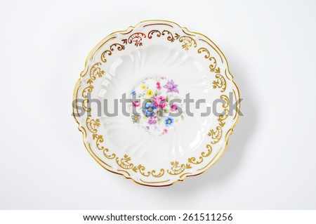 white decorative plate with floral pattern on white background - stock photo