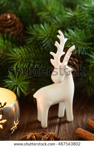 white deer christmas decoration on rustic background with candle lantern and fir branch - White Deer Christmas Decoration
