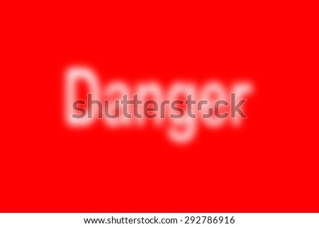 white defocused blur word Danger on red background - stock photo
