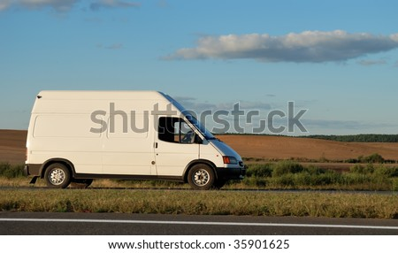 White delivery mini truck moving on the highway over blue sky. See my portfolio for trucks and lorries - stock photo
