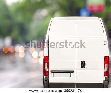 White delivery Van driving fast on city blurr bokeh street - stock photo
