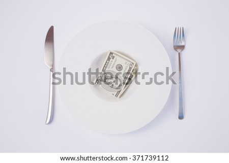 white design stylish round soup plate with wad of dollar cash money five banknote between silver fork and knife on white tablecloth - stock photo