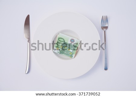 white design stylish round soup plate with wad of Euro cash money one hundred banknote between silver fork and knife on white tablecloth - stock photo