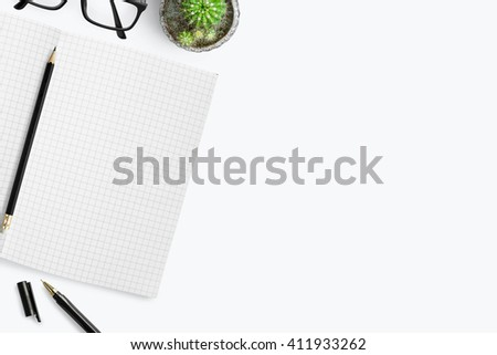 White desk with grid lined notebook and other supplies. Top view with copy space. - stock photo