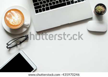 white desk with office supplies and laptop coffee latte atr and tablet, top view
