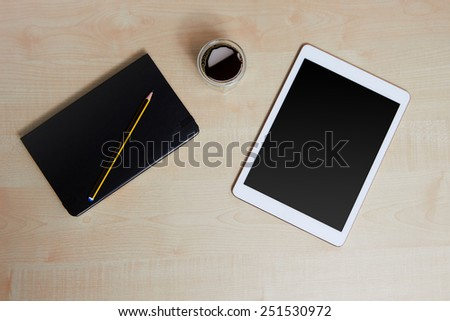 White digital tablet on a wooden desk with coffee and organiser