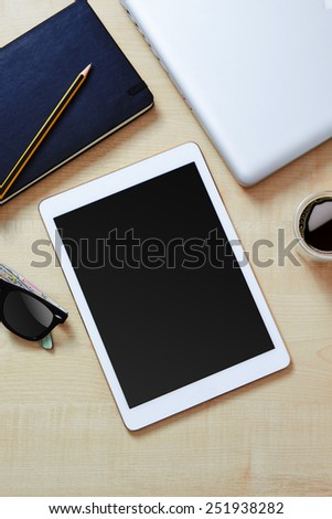 White digital tablet on a wooden desk, with laptop, coffee and a pair of sunglasses