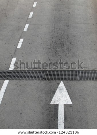 White  direction arrow and street  line  marked on black street - stock photo