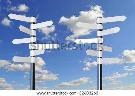 white direction signs on metal pole, against blue sky with white clouds