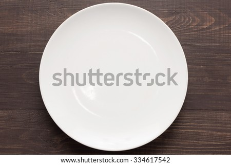 White dish on the wooden background. Top view. - stock photo
