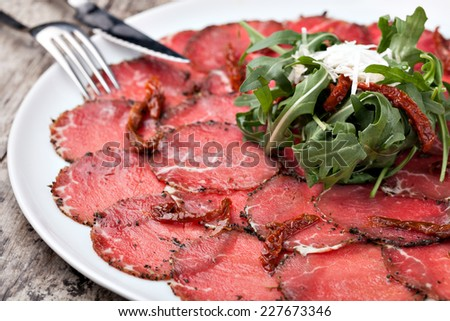 white dish with carpaccio of beef on arugula - stock photo