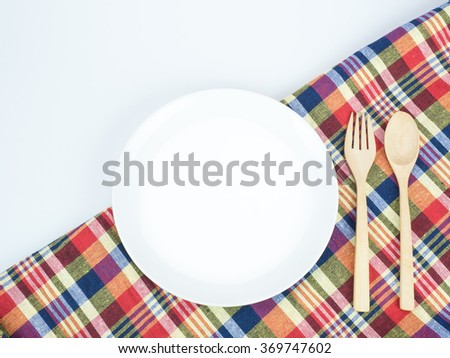White dish with wooden spoon and fork on colorful tablecloth.