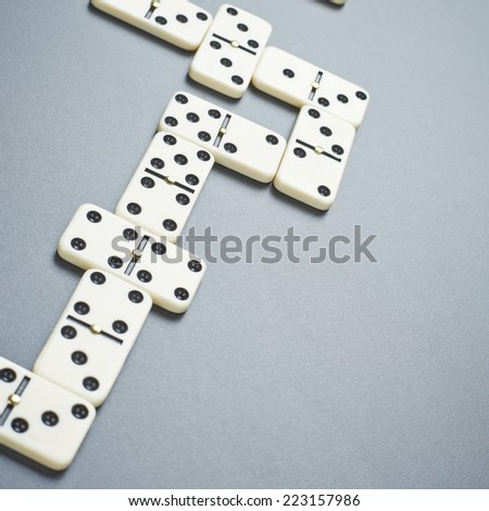 White domino bones composition over the gray background surface - stock photo