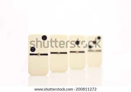 White dominoes with first one in focus