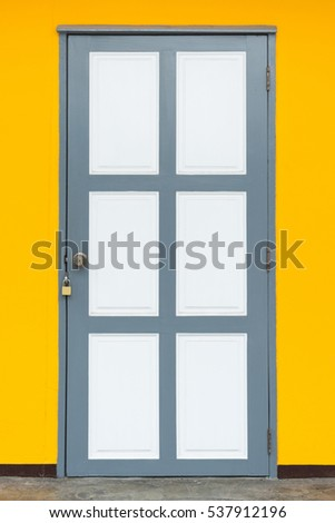 White door on yellow wall background.