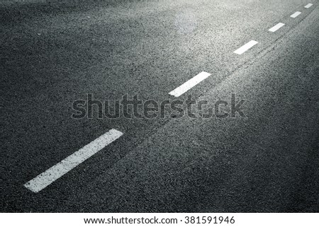 White dotted line on city asphalt road background. - stock photo