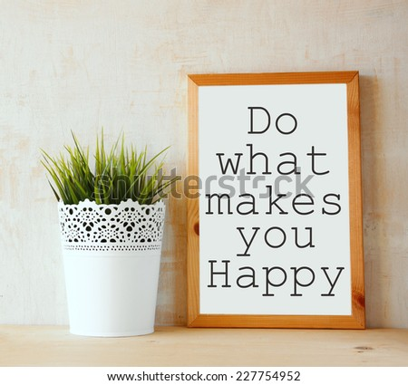 """white drawing board with the phrase """" do whats makes you happy """" written on it against textured wall - stock photo"""