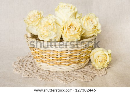 White dried roses in basket with knitted doily over linen background. - stock photo
