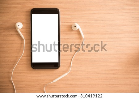 white earphones and smartphone on wooden background with copy space - vintage effect style picture - stock photo