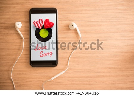 white earphones and smartphone show love song on screen on wooden background with copy space - vintage effect style picture. Valentine's day. Love song or music concept. - stock photo
