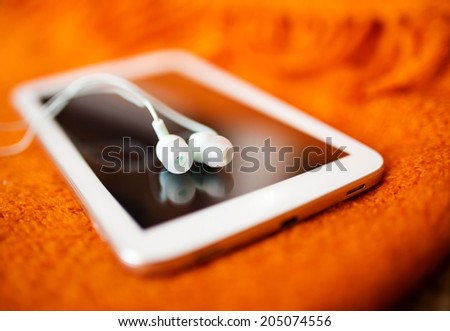 White earphones and tablet pc, close up photo, small dof - stock photo