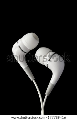 White earphones isolated over black background - stock photo