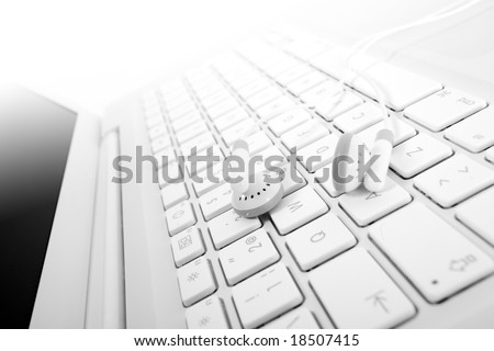 White earphones over a white keyboard suggesting mp3 online buy or download. Small DOF. Focus is on left earphone.