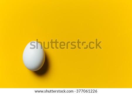 White egg on the yellow background. Design, visual art, minimalism - stock photo
