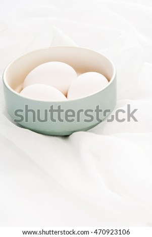 White eggs isolated in bowl over soft fabric background.