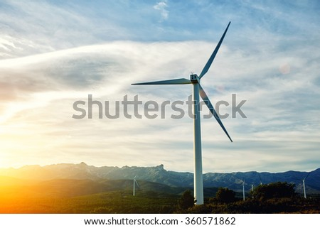 White electric generator in field against evening cloudy sky, wind turbine located in countryside with sunset on background, renewable and alternative energy sources - stock photo