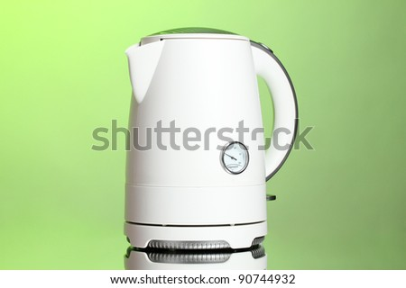 White electric kettle on green - stock photo