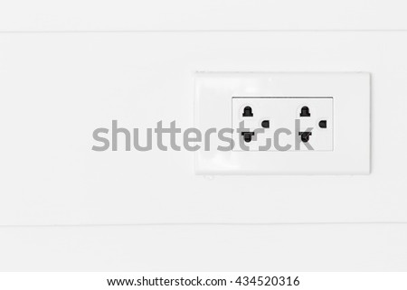 White electric plugs on white wood wall, with copy space background. - stock photo