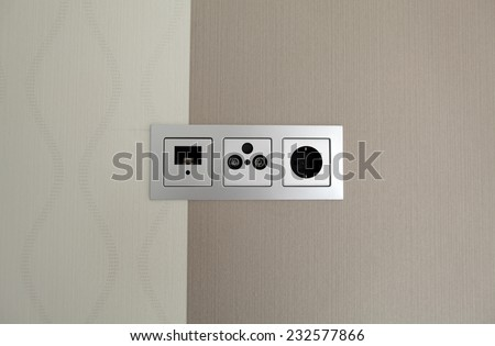 White electric socket and connector on the modern wall with pattern. Close up. - stock photo