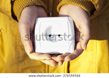 White electric socket in hands. A man hold the electric socket. Hand holding an electric outlet - stock photo