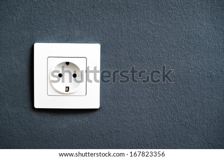 White electrical outlet socket on gray room wall - stock photo