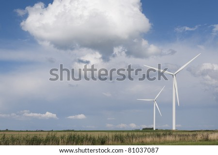 White electrical power generating wind turbines under a blue sky