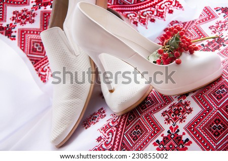 White elegant, stylish wedding (bridal) shoes (bride'??s and groom'??s ) are on a red embroidery ukrainian background with red guelder rose (viburnum opulus, berries). Close up. Ukraine. - stock photo