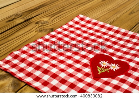 White embroidered Edelweiss flower on heart appliques on the checkered red white tablecloth on wooden table rustic background - stock photo