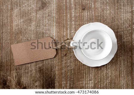 White empty cup with paper blank tag on wooden background