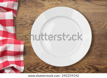 white empty dinner plate setting on wooden table with tablecloth - stock photo