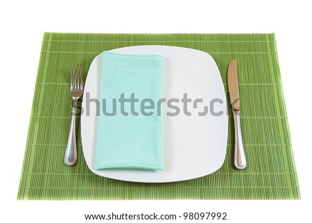 White empty dinner plate with napkin, fork and knife on bamboo placemat