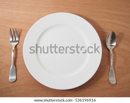 White empty dish with stainless spoon and  fork on wooden table