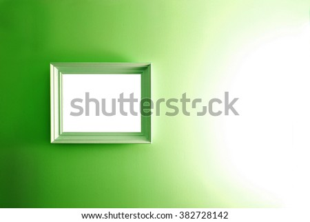 White empty frame on the green wall. Free copy space. - stock photo