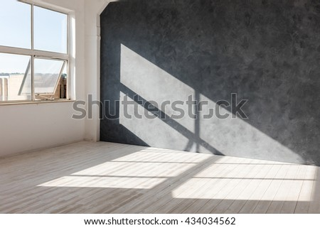 White empty loft interior with dark wall and window shadow. Daylight studio interior with white wood floor and large industrial window. Space concept.