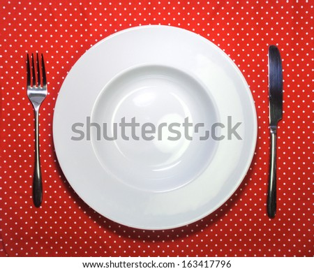 White empty plate, fork and knife on red cloth with polka dots - stock photo