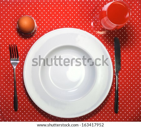 White empty plate, fork, knife, juice and egg on red cloth with polka dots