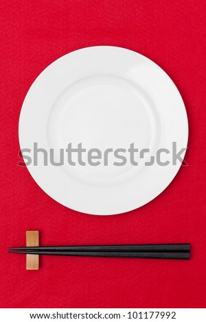 White empty plate with chopsticks on red tablecloth - stock photo