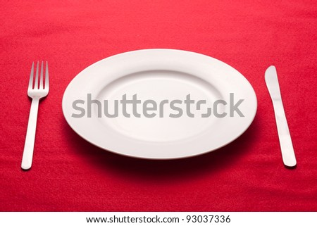 White empty plate with fork and knife on a red tablecloth - stock photo