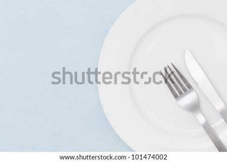 White empty plate with fork and knife on light blue tablecloth - stock photo